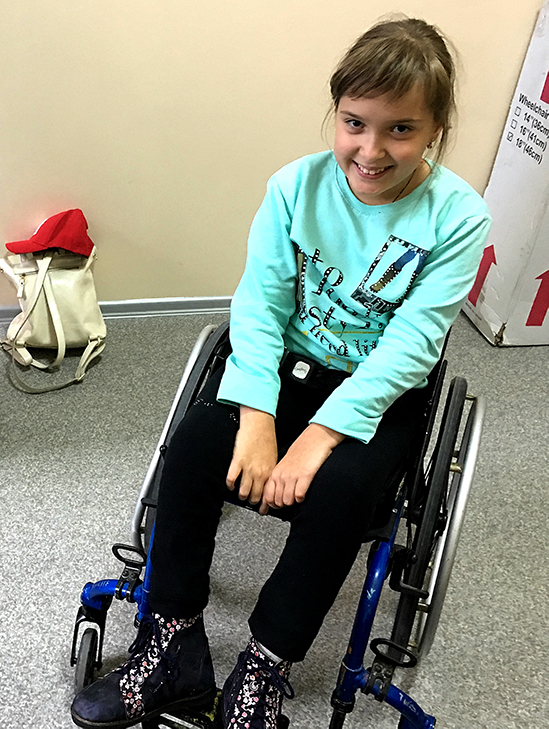 Young girl smiling in modern wheelchair